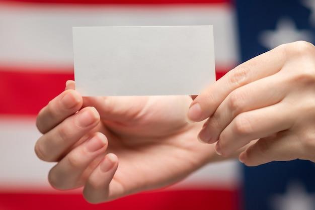 여자 손에 빈 카드입니다. 공간을 복사합니다. 미국 국기 배경입니다.
