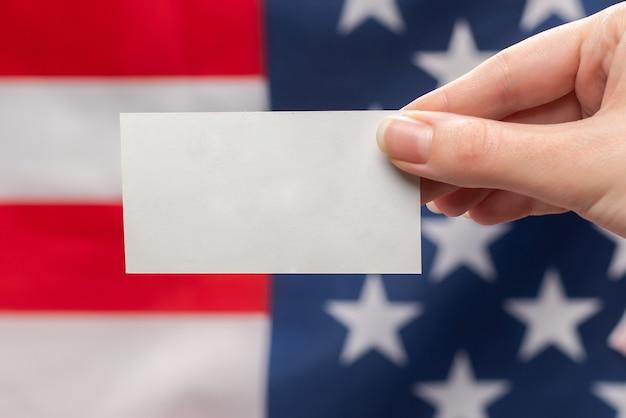 女性の手に空のカード。スペースをコピーします。アメリカの国旗の表面。