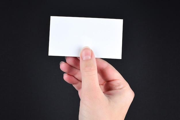 Пустая карточка в руке женщины на черной предпосылке.