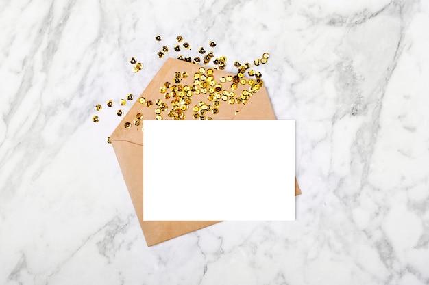 Пустая карточка с конвертом и золотым конфетти. шаблон макета. вид сверху