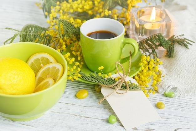 軽い木製のテーブルにミモザ、レモン、コーヒーと空のカード