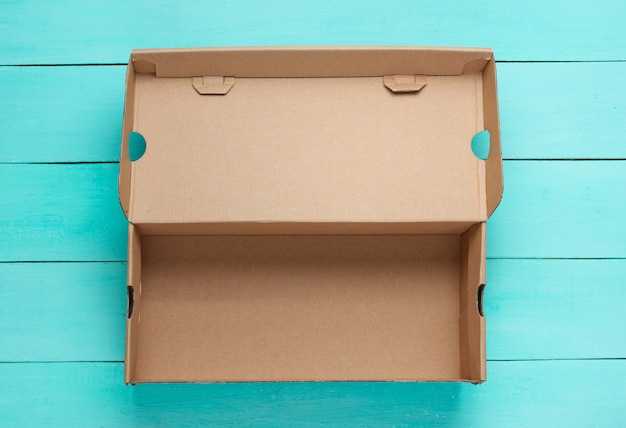 Empty cardboard box on blue wooden surface.