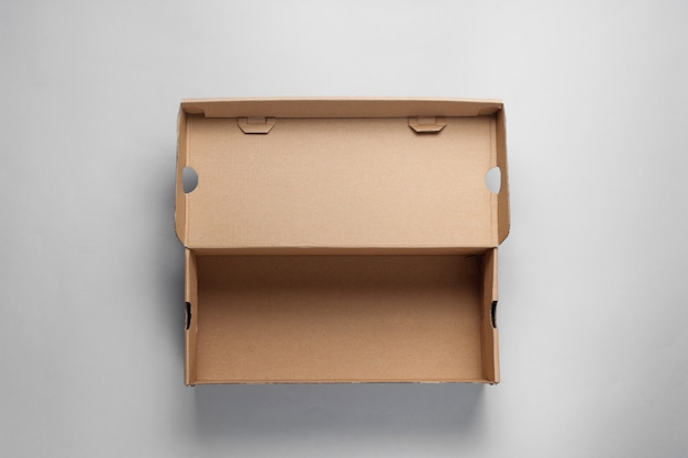 Empty cardboard box on gray surface.