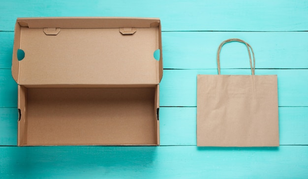 Empty cardboard box and paper bag on blue wooden surface.