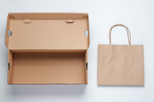 Empty cardboard box and paper bag on white surface.