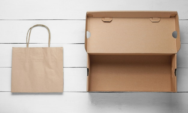 Empty cardboard box and paper bag on white wooden