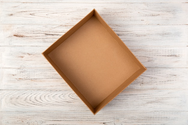 Empty cardboard box on a white wooden background top view