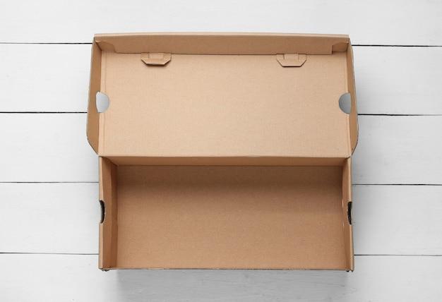 Empty cardboard box on white wooden