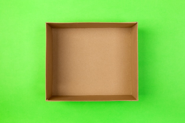 Empty cardboard paper box on green. delivery concept, top view