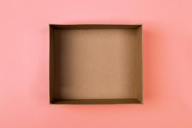 Empty cardboard paper box on orange