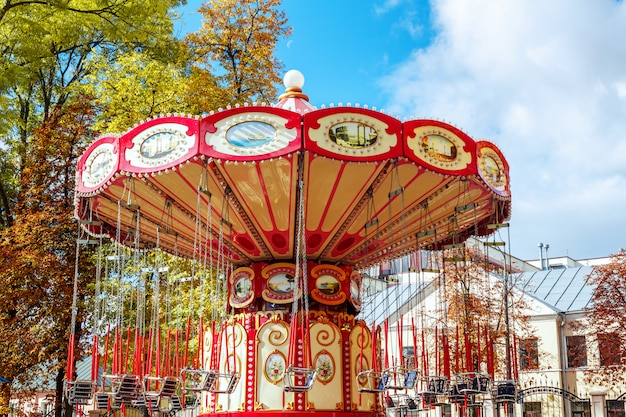 Empty carousel merry-go-round with seats suspended on chains