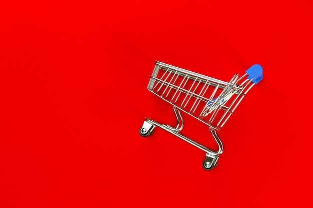 Empty cart trolly for shopping product in super market on red background