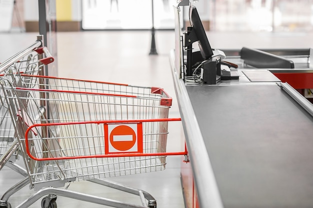Empty cash desk with closed way border in supermarket.