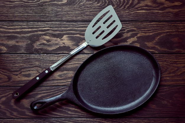Empty cast iron frying pan and a culinary spatula on wooden background, top view