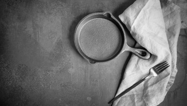 Пустая чугунная сковорода на темном фоне