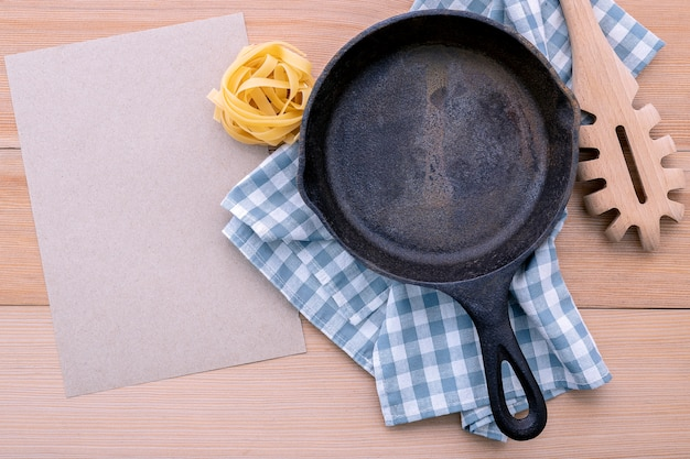 Empty cast iron skillet and  pasta ladle on wooden table.