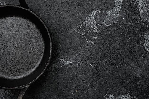 Пустая чугунная сковорода с копией пространства для текста или еды с копией пространства для текста или еды, плоская планировка, вид сверху, на черном фоне темного каменного стола
