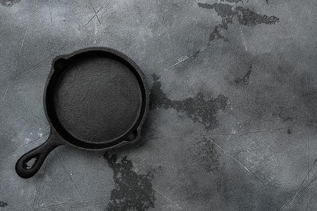 Пустая чугунная сковорода с копией пространства для текста или еды с копией пространства для текста или еды, плоская планировка, вид сверху, на фоне серого каменного стола