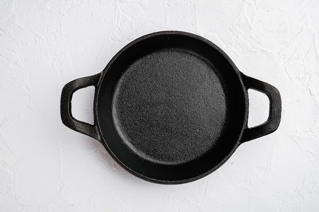 Пустая чугунная сковорода с копией пространства для текста или еды с копией пространства для текста или еды, плоская планировка, вид сверху, на фоне белого каменного стола