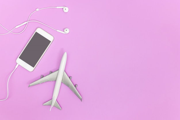 Empty cell phone with travel concept on pink copy space