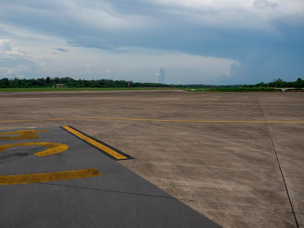 Empty cement runway road in countryside airport with rain clouds sky