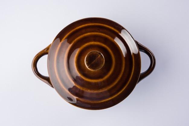 뚜껑이나 바르니가 있는 빈 세라믹 그릇 또는 용기, 일반 배경 위에 격리