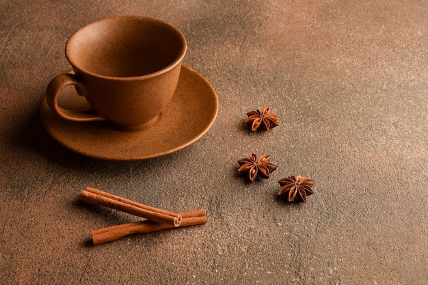 돌 표면에 접시, 계피, 아니스가 있는 빈 세라믹 갈색 컵