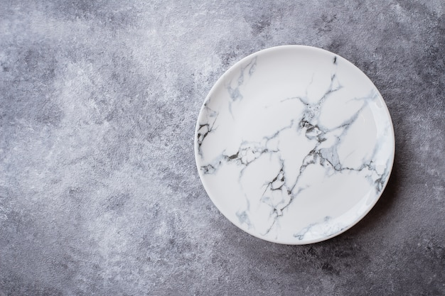 Empty ceramic marble plate on gray stone concrete table background.
