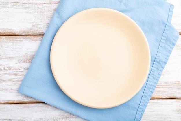 흰색 나무 배경 및 파란색 리넨 섬유에 빈 세라믹 접시. 평면도, 클로즈업, 평평하다.