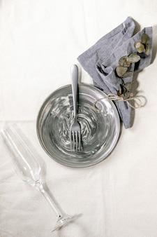 Пустая керамическая тарелка с вилкой, бокалом шампанского и текстильной салфеткой