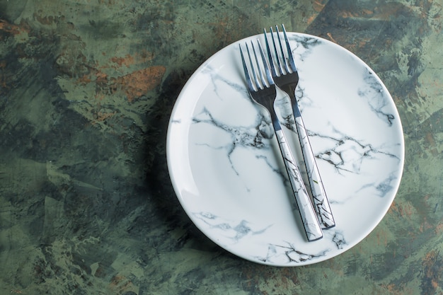 Empty ceramic plate with fork over green concrete background. top view with copy space. flat lay.