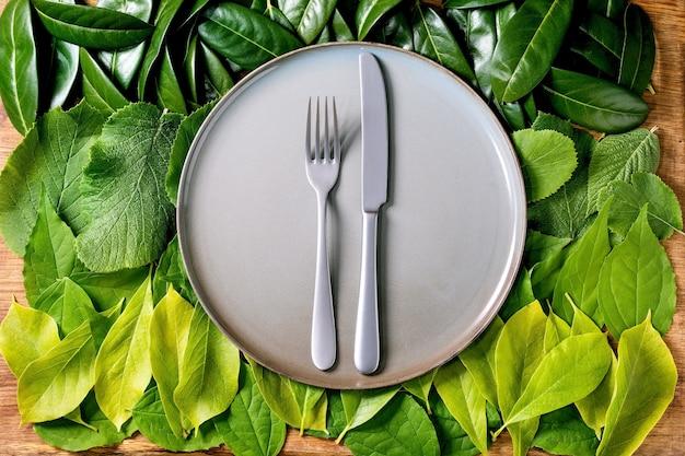 나이프와 포크 녹색 잎, 녹색 그라데이션의 배경에 빈 세라믹 접시. 공간을 복사하십시오. 제품을위한 빈 장소. 여름 메뉴 개념. 자연 창의적인 레이아웃, 평평한 평신도, 친환경 음식