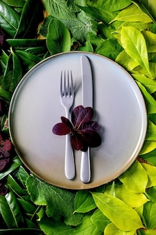 Пустая керамическая тарелка с ножом и вилкой на фоне из зеленых листьев, зеленый градиент. пустое место для продукта. концепция эко-еды летнего меню. творческий макет природы, вид сверху, плоская планировка