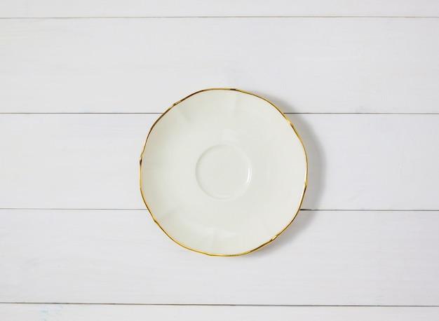 白い木のテーブルの背景に空のセラミック円形のプレート。上面図