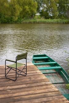 空の椅子と湖のそばの木製の桟橋、桟橋近くの緑のボートの釣り竿。屋外レクリエーション。