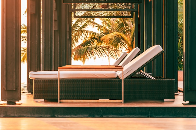 Empty chair around swimming pool in hotel and resort for leisure travel