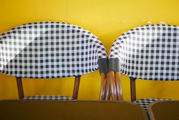 노란색 배경에 카페의 빈 의자