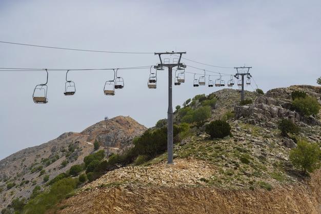 Пустой кресельный подъемник на склоне горы летом