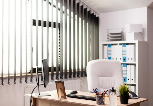 インテリアに自然光が差し込むオフィスの職場には誰もいない空の椅子。オフィス内のデスクトップコンピュータとビジネスノートでテーブルを管理します。