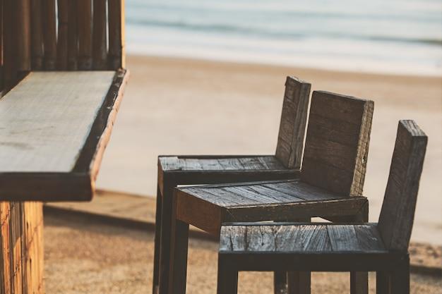 Empty chairs at bar near beach