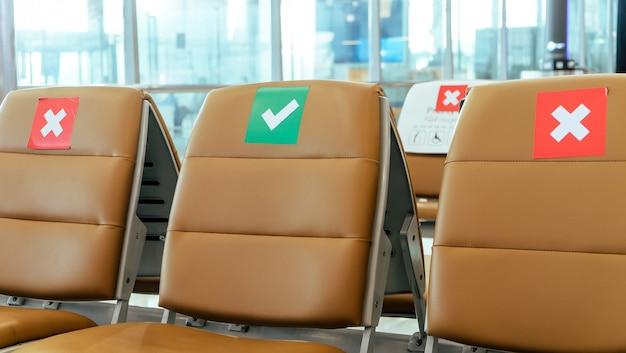 Пустые стулья в зоне вылета аэропорта, отмеченные символами социального дистанцирования