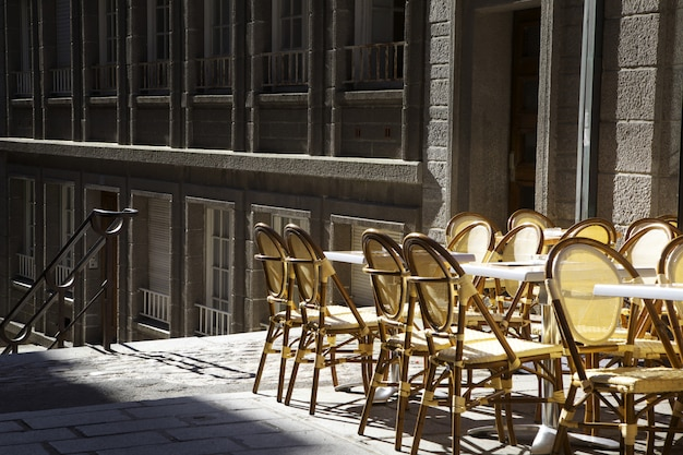 Empty chairs outside the bar in the morning