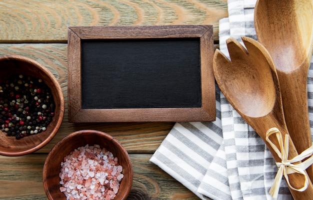 古い木製のテーブルの上のスパイスと空のチョークボードと台所用品