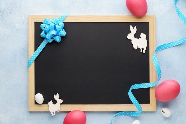 空の黒板とバニーとピンクの卵とイースターの装飾