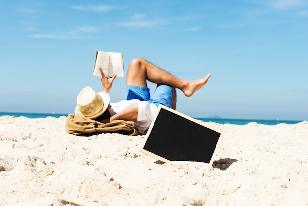 Empty chalkboard on beach sand with young tourist man laying down on the beach and reading a book in