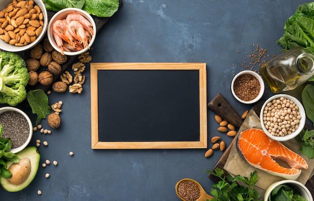 オメガ3の食物源と健康的な脂肪を含むテキスト用の空の黒板。野菜、魚介類、ナッツ、種子などの脂肪酸を多く含む食品