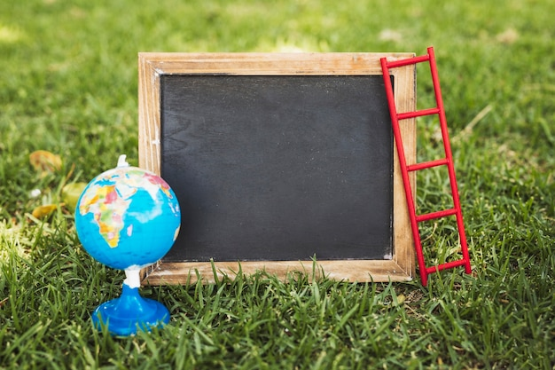 Empty chalkboard and globe on nature