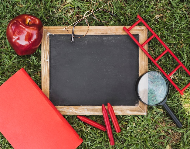 Empty chalkboard near stationery, glasses and apple on grass