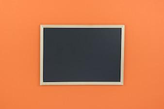 Empty chalkboard on orange background with copy space.