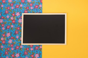 Empty chalkboard on yellow background with copy space.